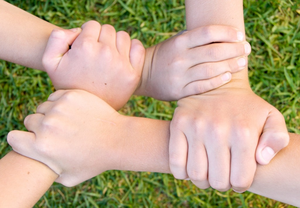 children's hands clasped together to form the shape of a square with their linked wrists