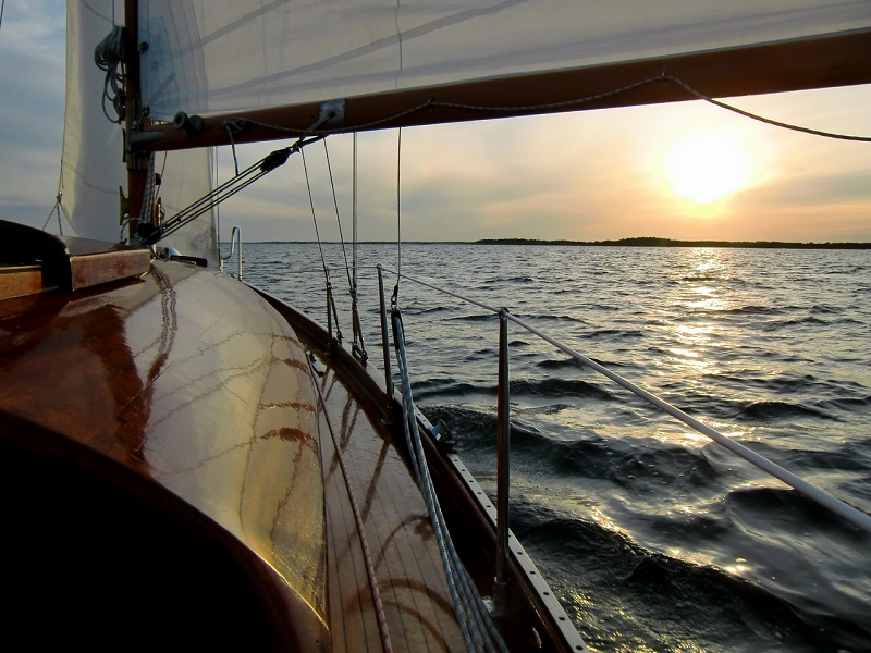 shiny wooden bow of a sailboat gliding over waters during a sunset