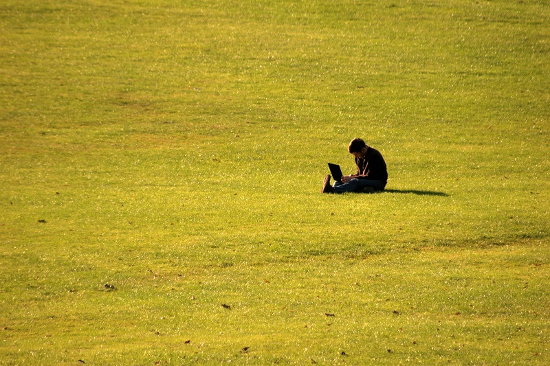 Student sitting alone in a large field studying
