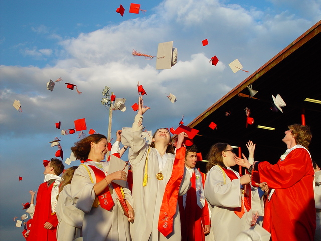 A large group of high school students stand outside their school throwing their graduation caps up in the air