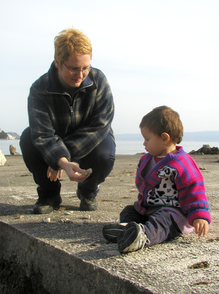 Mother bending to show child a rock outsdie