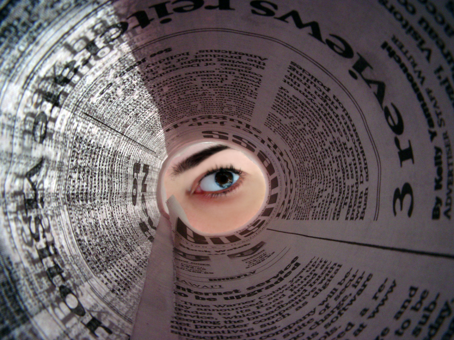 eye looking through a rolled up newspaper like a telescope