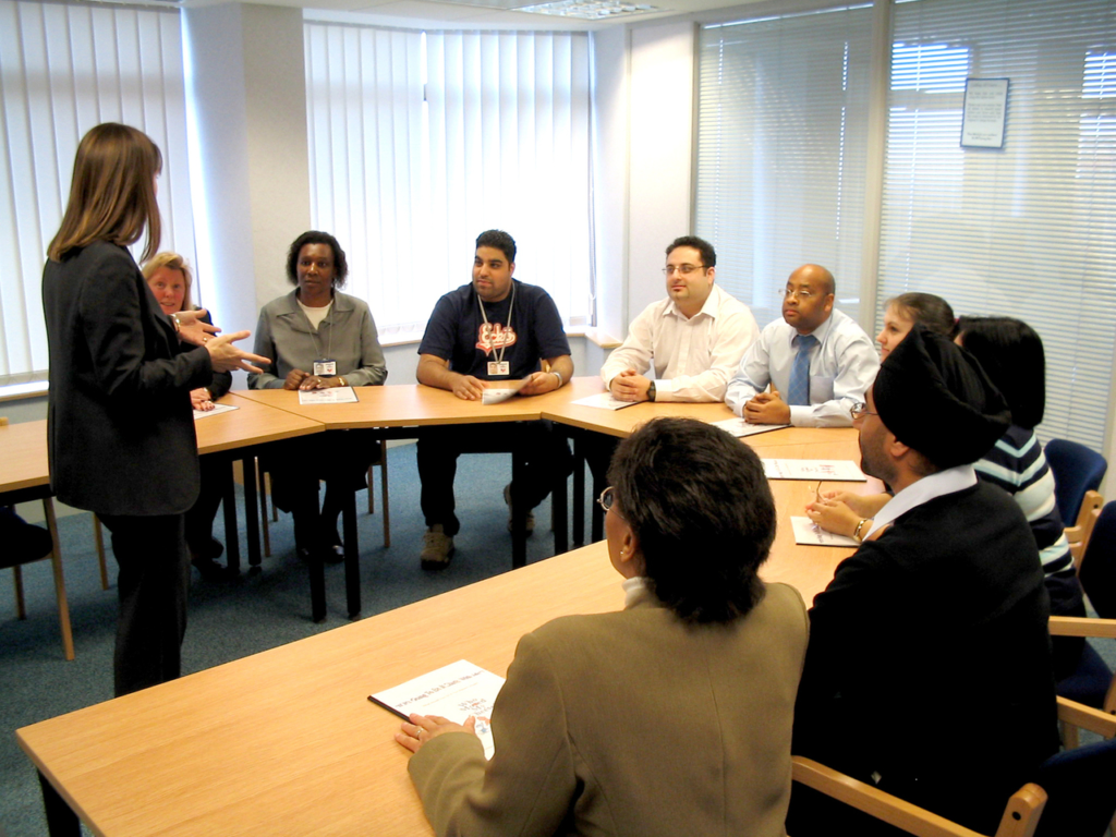 Woman standing in front of a table with a diverse group of people sitting around it an listening to her speaking