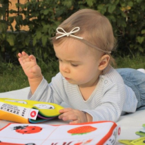 toddler laying on tummy on a blanket on the grass looking at a baby book