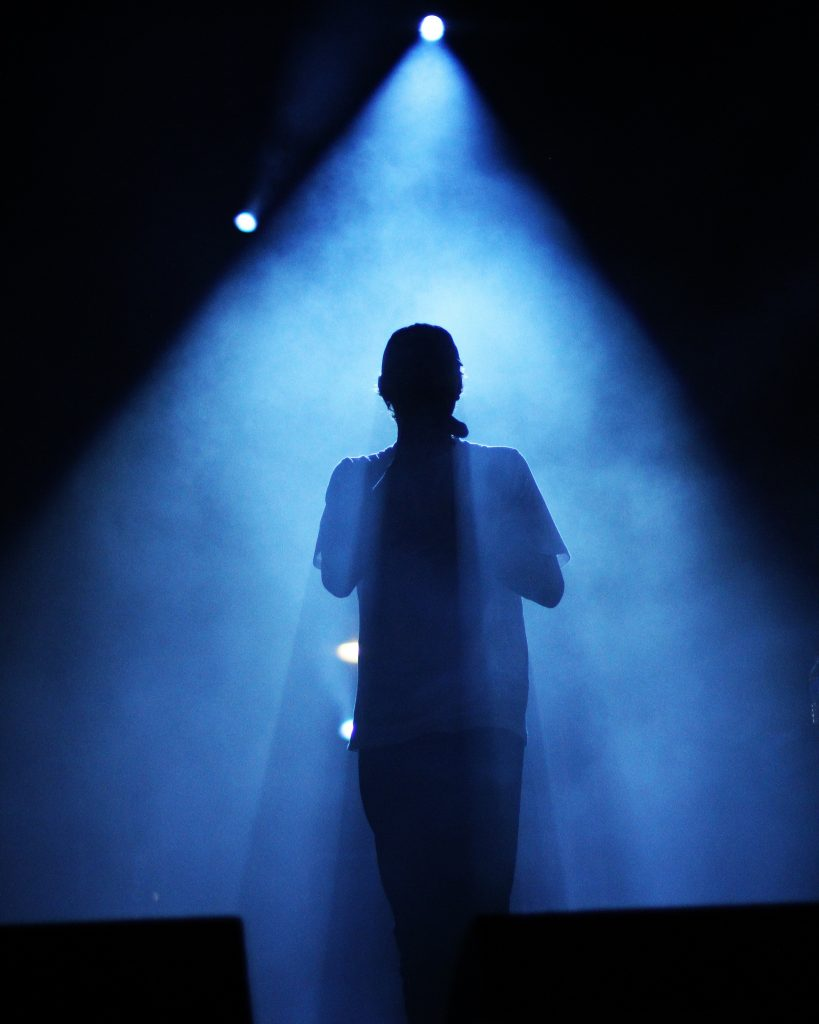 rear view of a person silhouetted on stage surrounded in blue light
