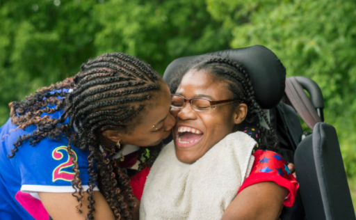African American mother bends down to kiss her daughter on the cheek. The daughter is in a wheelchair