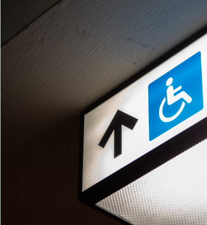 part of a lighted sign with an arrow pointing up and the blue handicap wheelchair icon